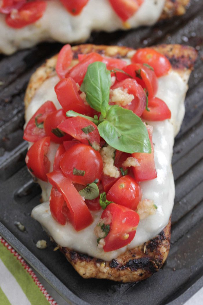 Bruschetta Chicken on a grill pan with tomatoes and basil on top