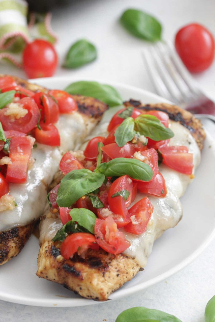 Bruschetta Chicken on a white plate with tomatoes and basil on top