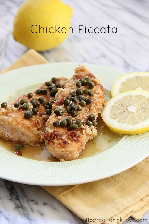 Chicken Piccata on a green plate with lemon slices and capers on top