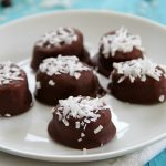 Chocolate-Covered Banana slices with shredded coconut on top on a white plate