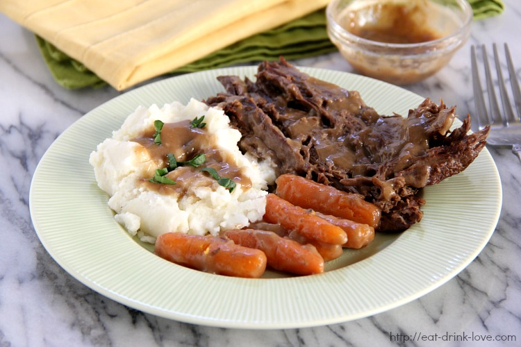 Crockpot Pot Roast on a plate with potatoes and gravy