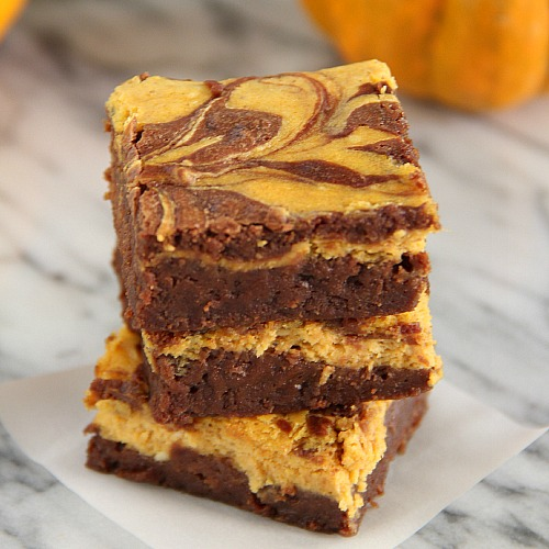 Mocha Pumpkin Cheesecake Brownies stacked with a pumpkin