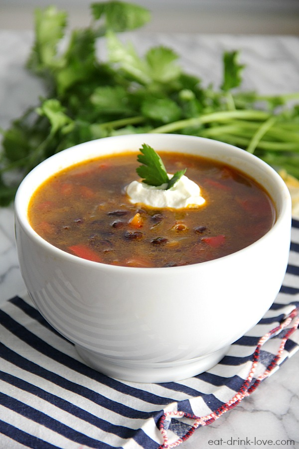 Spicy Black Bean Soup in a white bowl on a blue striped napkin