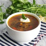 Spicy Black Bean Soup on a white bowl with a blue striped napkin