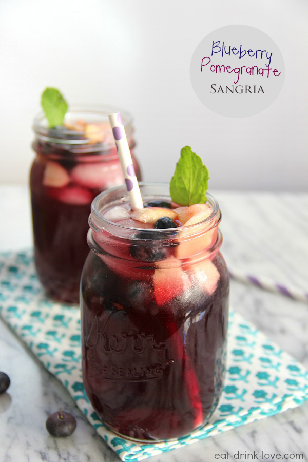 Blueberry Pomegranate Sangria in jar with a straw, fruit, mint leaves