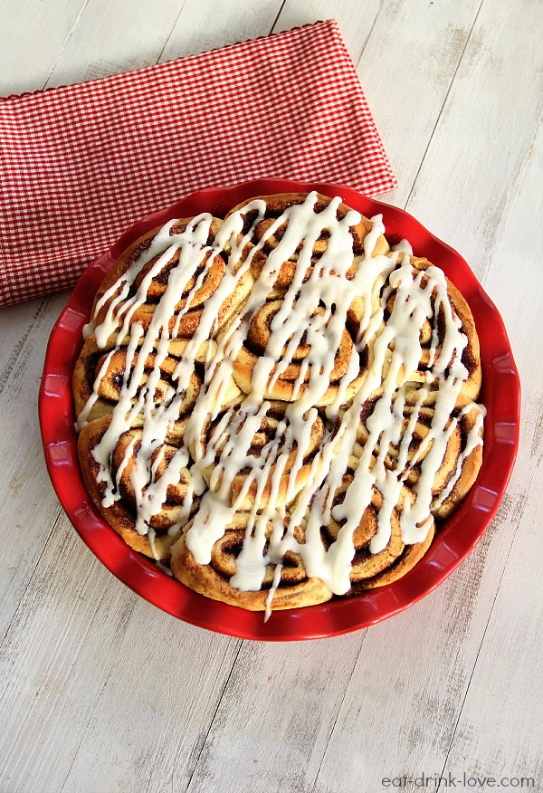 1-Hour Cinnamon Rolls with cream cheese drizzle in a red pie dish