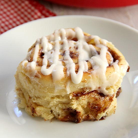 homemade cinnamon roll with cream cheese drizzle on a white plate
