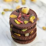 Dark Chocolate Fruit and Nut Cups stacked on a white marble board