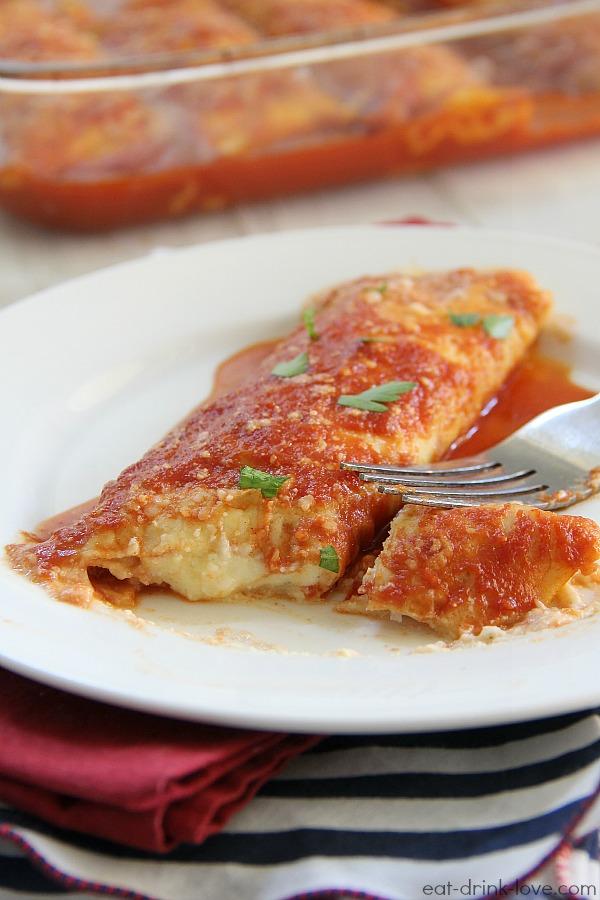 Homemade Manicotti on a white plate with marinara sauce