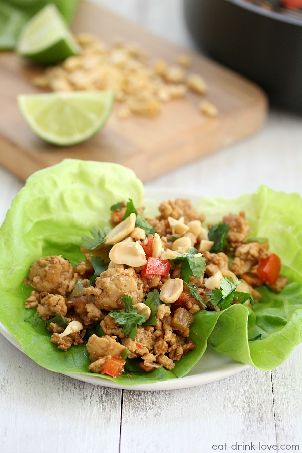 Thai Peanut Chicken Lettuce Wraps on a plate with peanuts and lime slices