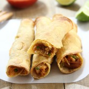 Baked Chicken Taquitos stacked on a wooden board with lime slices