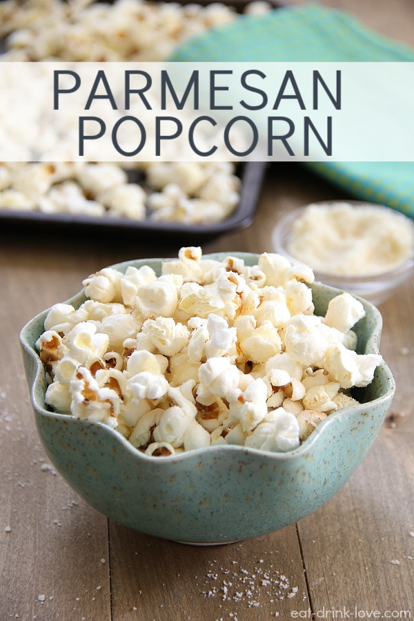 Parmesan Popcorn in a blue bowl on a wooden board