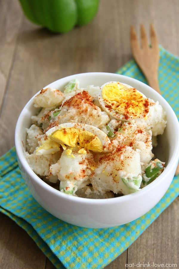 Dad's Potato Salad in a white bowl with paprika sprinkled on top