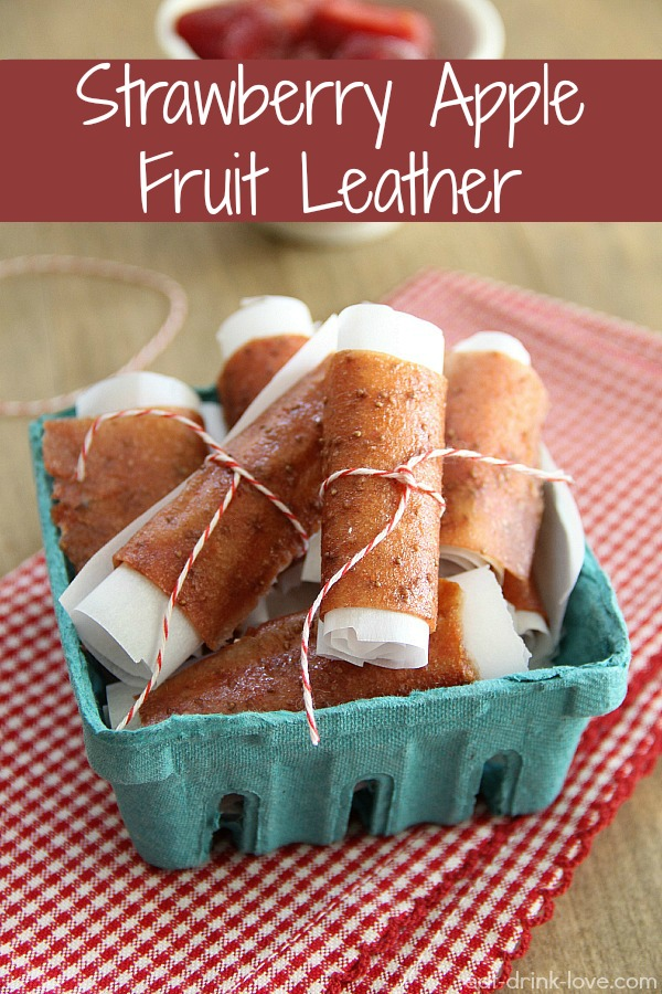 Strawberry Apple Fruit Leather rolls in parchment paper in a green basket