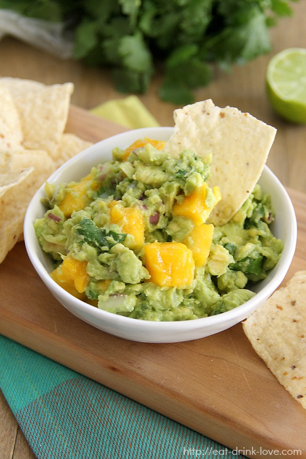 Mango Guacamole in a white bowl with lime and cilantro