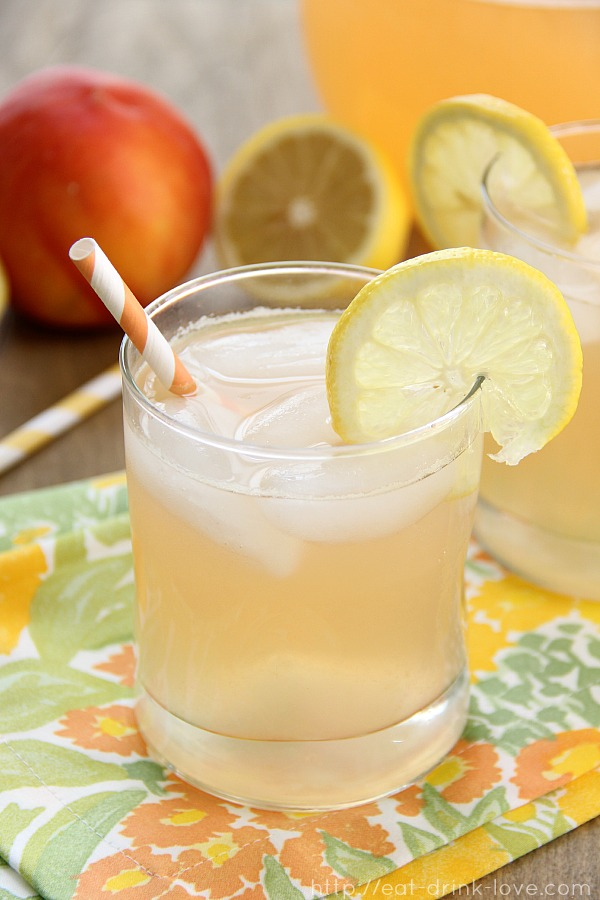 Peach lemonade in a glass with a lemon slice, straw, and floral napkin