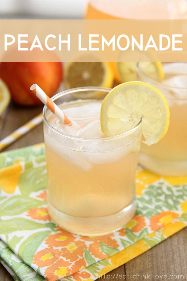 Peach Lemonade in a glass with a lemon, orange straw, and floral napkin