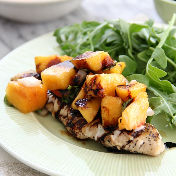 Peach Bruschetta Chicken - grilled chicken topped with peach salsa on a plate with arugula
