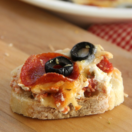 Pizza dip scooped on top of sliced bread