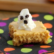 Pumpkin Cheesecake Bars on a wooden board with whipped cream ghosts on top on a polka dot napkin