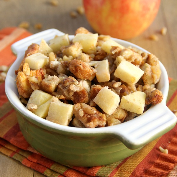 Apple Walnut Stuffing in a green ramekin with apples on top and an apple in the background on a striped napkin
