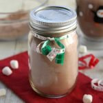 Hot Cocoa mix in a glass jar on red napkin with a green ribbon