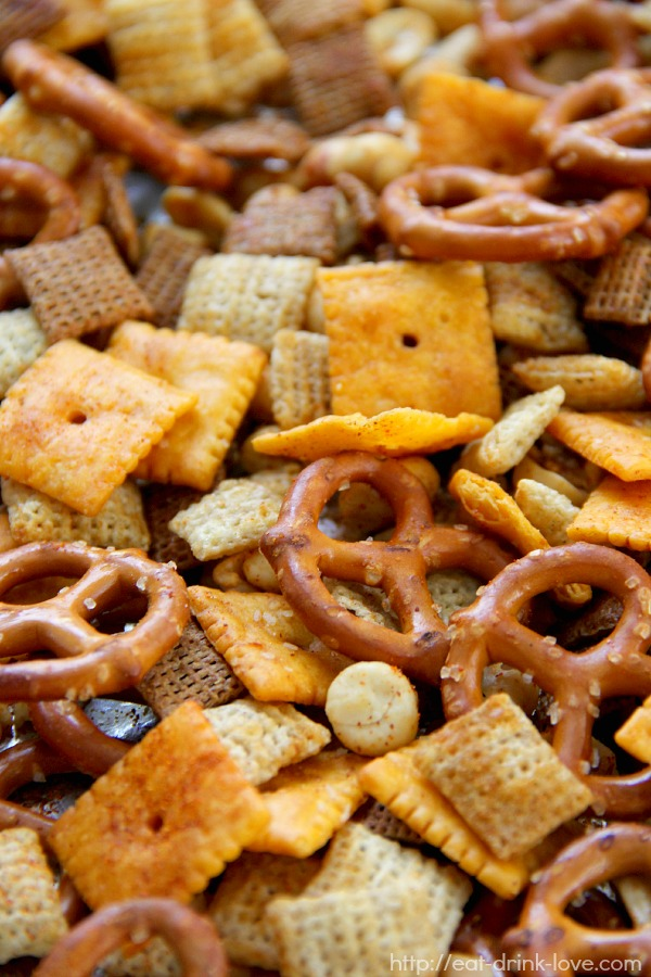 Spicy Chex Mix - pretzels, cheese crackers, nuts, and wheat cereal tossed and baked in sriracha sauce on a baking sheet