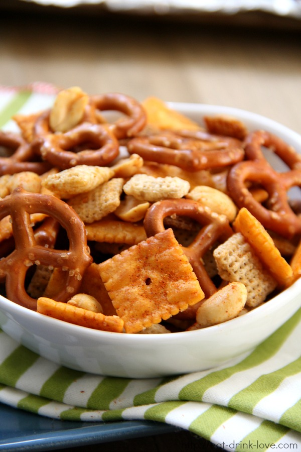 Spicy Chex Mix - pretzels, cheese crackers, nuts, and wheat cereal tossed and baked in sriracha sauce in a white bowl