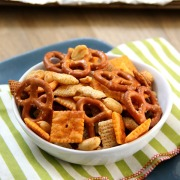 Spicy Chex Mix - cheese crackers, wheat cereal, pretzels, and nuts baked with a blend of chili powder and curmin in a white bowl