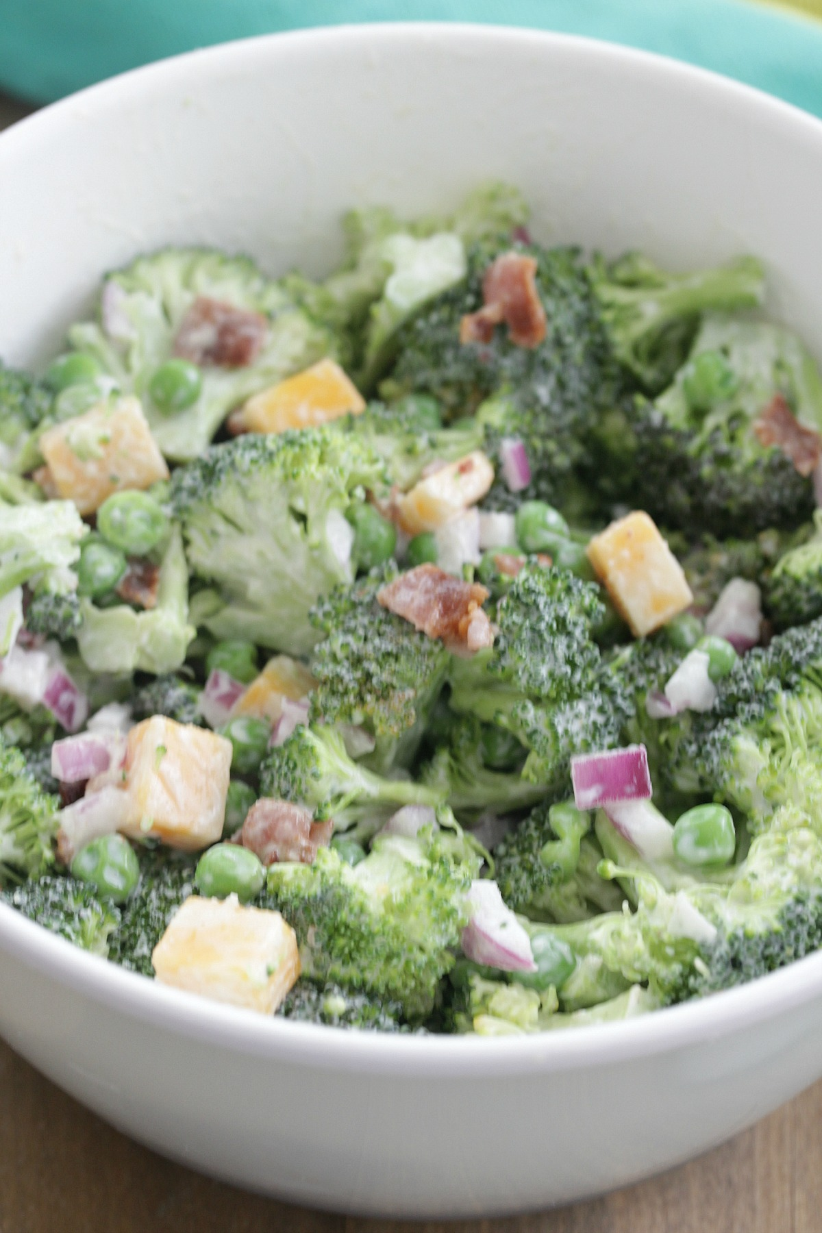 Overhead shot of bowl of broccoli salad with onion, bacon, peas, and cheese