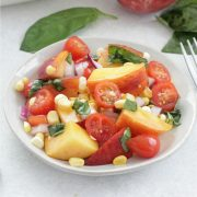 Peach and Tomato Salad on a white plate with basil and peaches