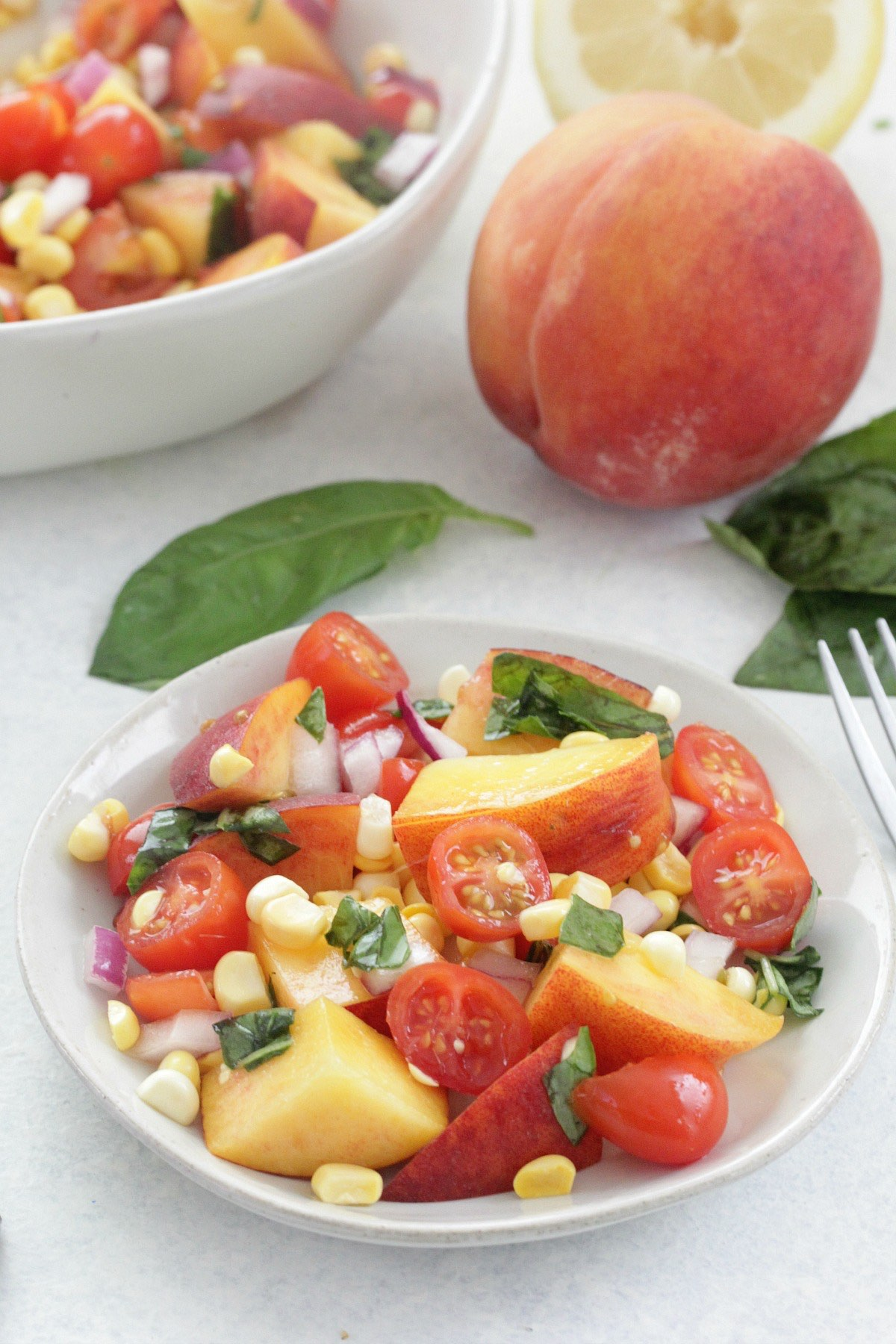 Peach and Tomato Salad on a white plate with fresh basil leaves and a peach