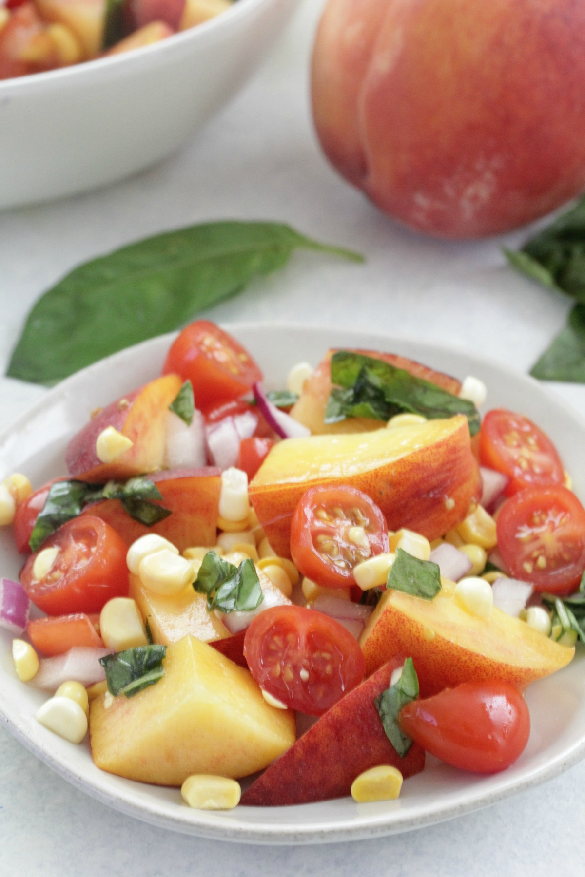Peach and Tomato Salad on a white plate with a peach