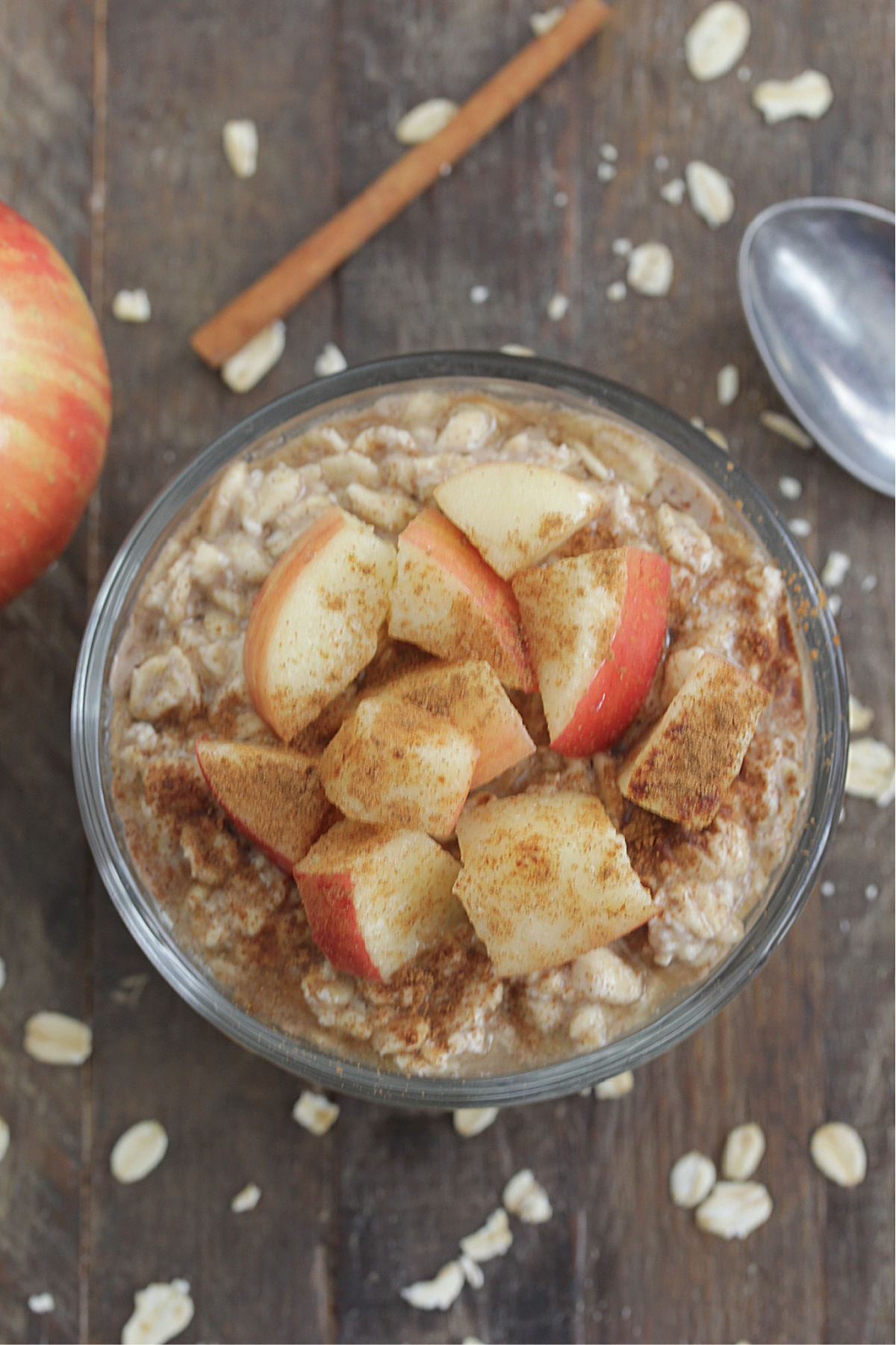 Overhead shot of Apple Cinnamon Overnight Oats in a glass jar with diced apples and cinnamon on top