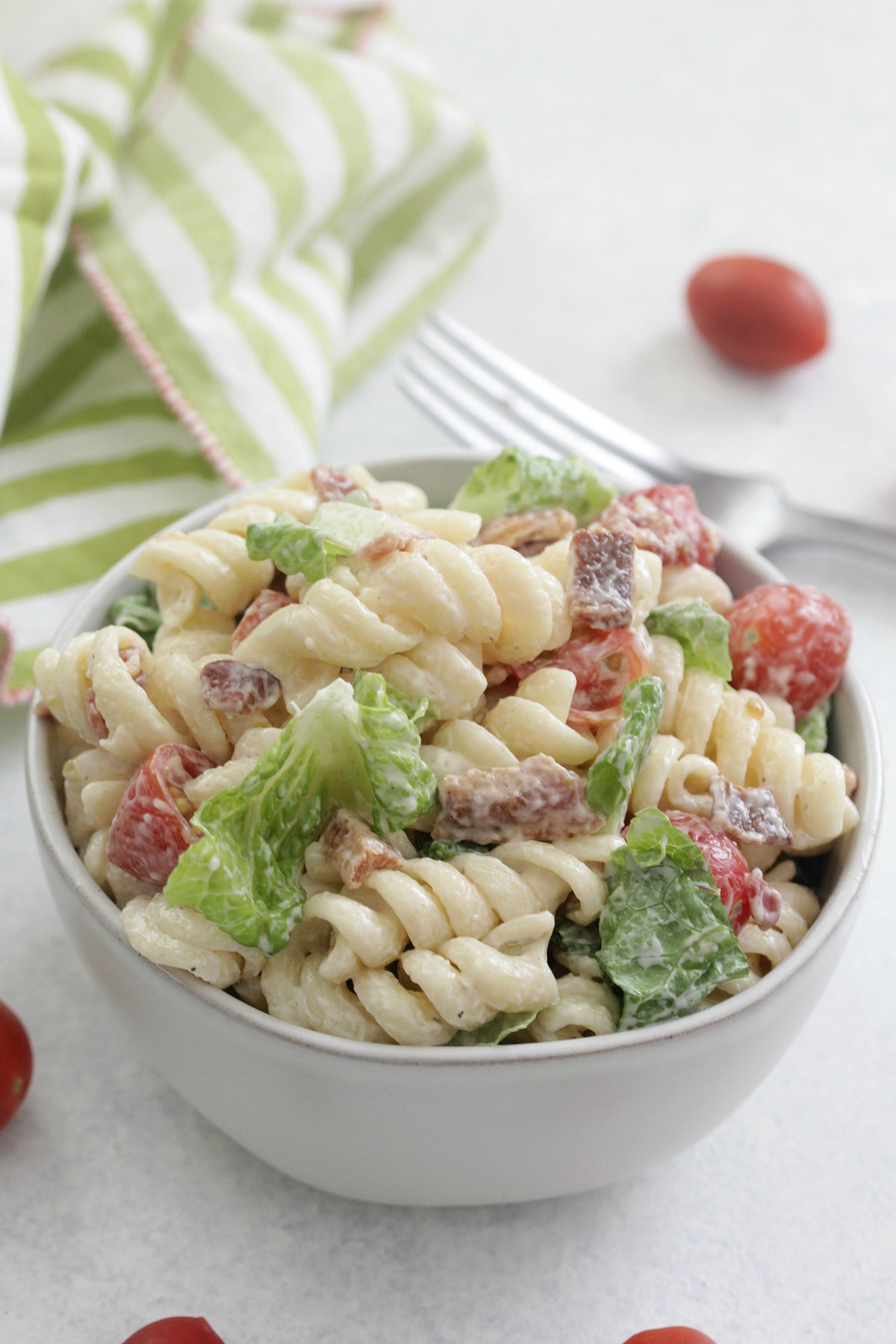 BLT Pasta Salad in a white bowl with a green striped napkin