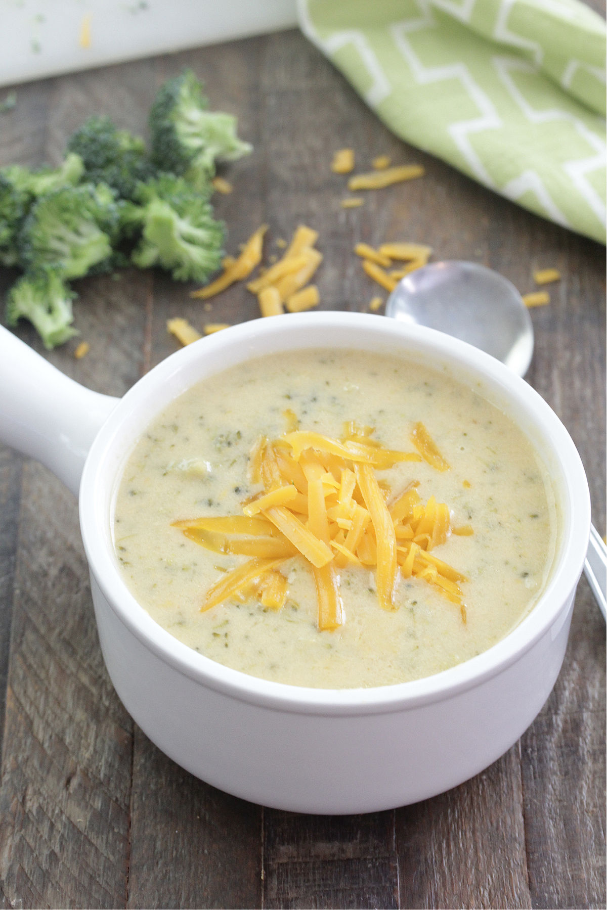 Instant Pot Broccoli Cheddar Soup in a white bowl with grated cheddar cheese on top
