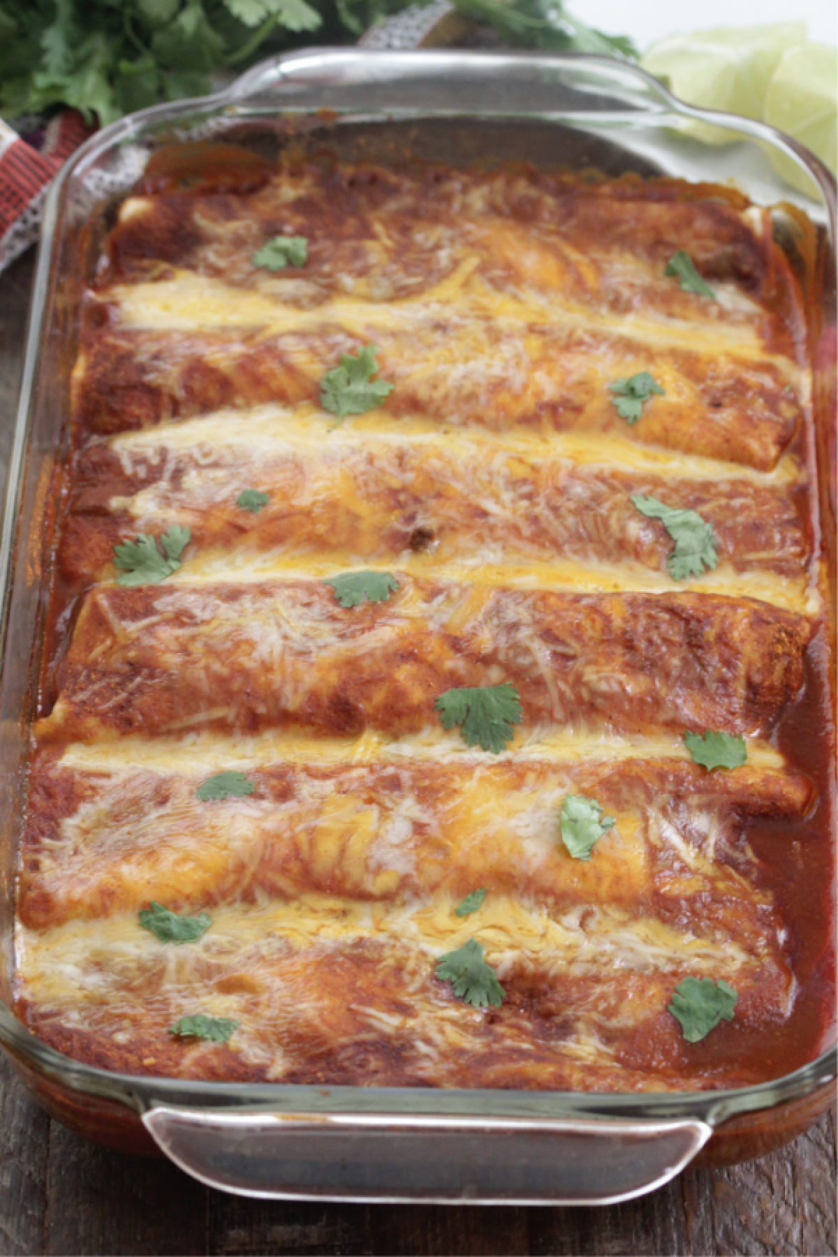 Spicy Beef Enchiladas in a baking dish with cheese on top