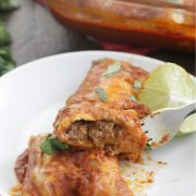 Spicy Beef Enchiladas on a white plate with a slice of lime