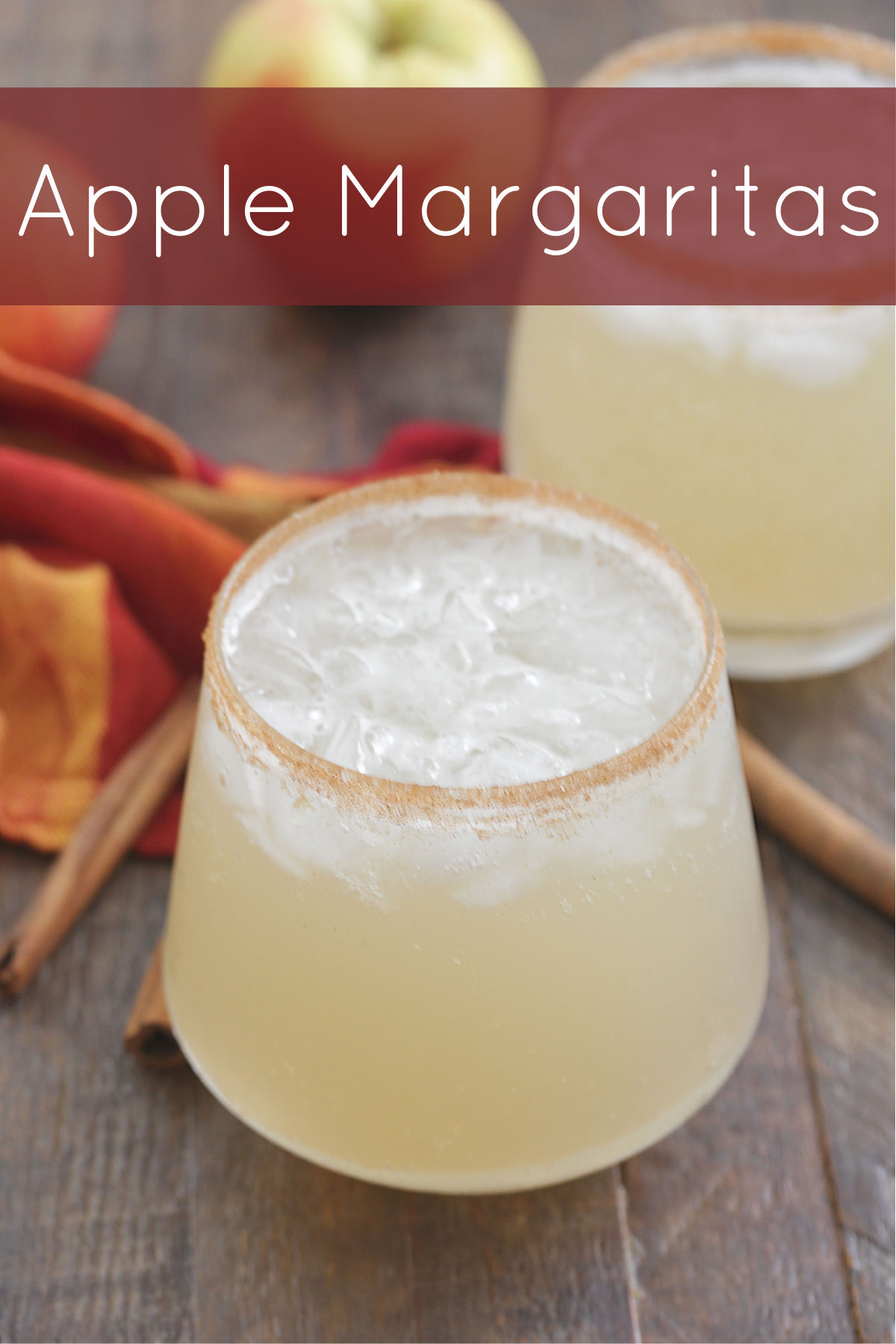 Apple Margaritas in a glass with a cinnamon sugar rim and apples