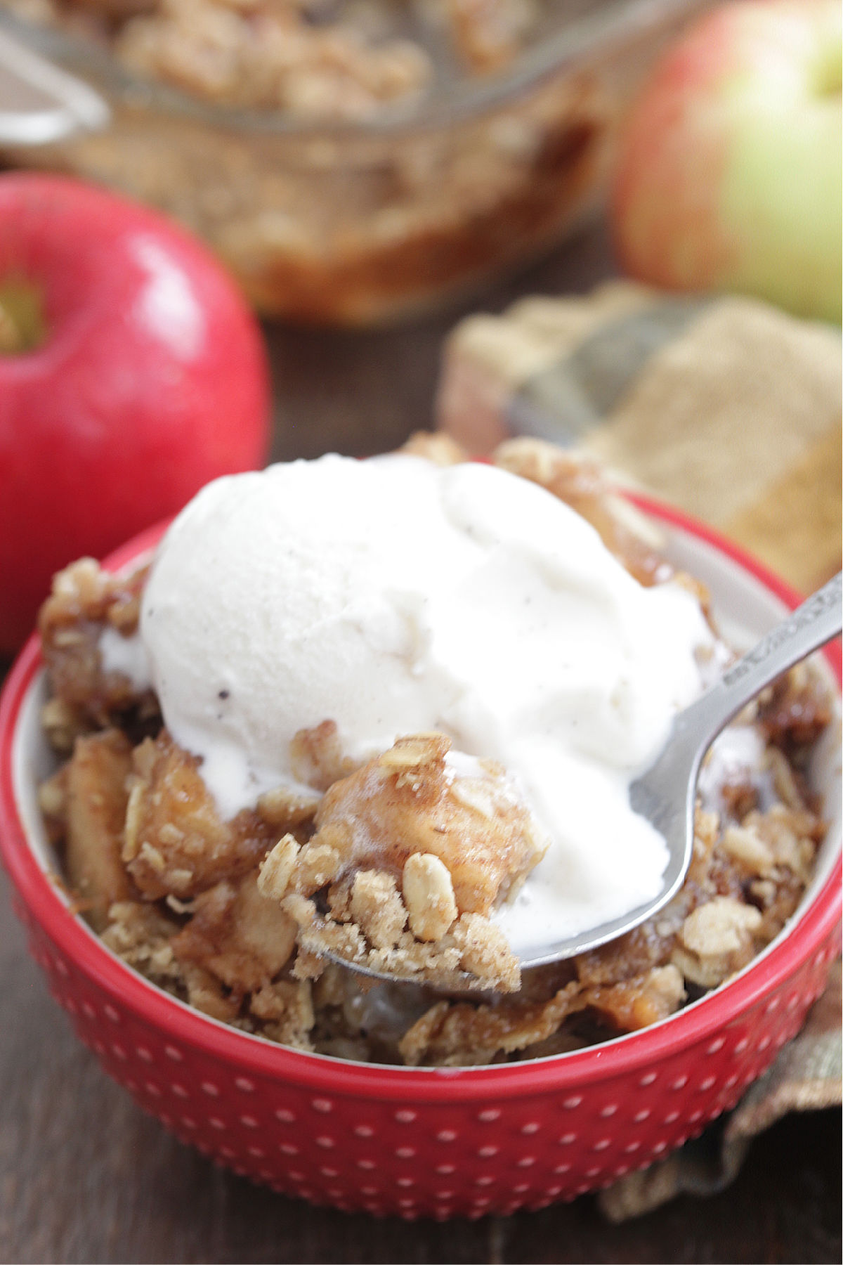 Caramel Apple Crisp in a red bowl with vanilla ice cream on top