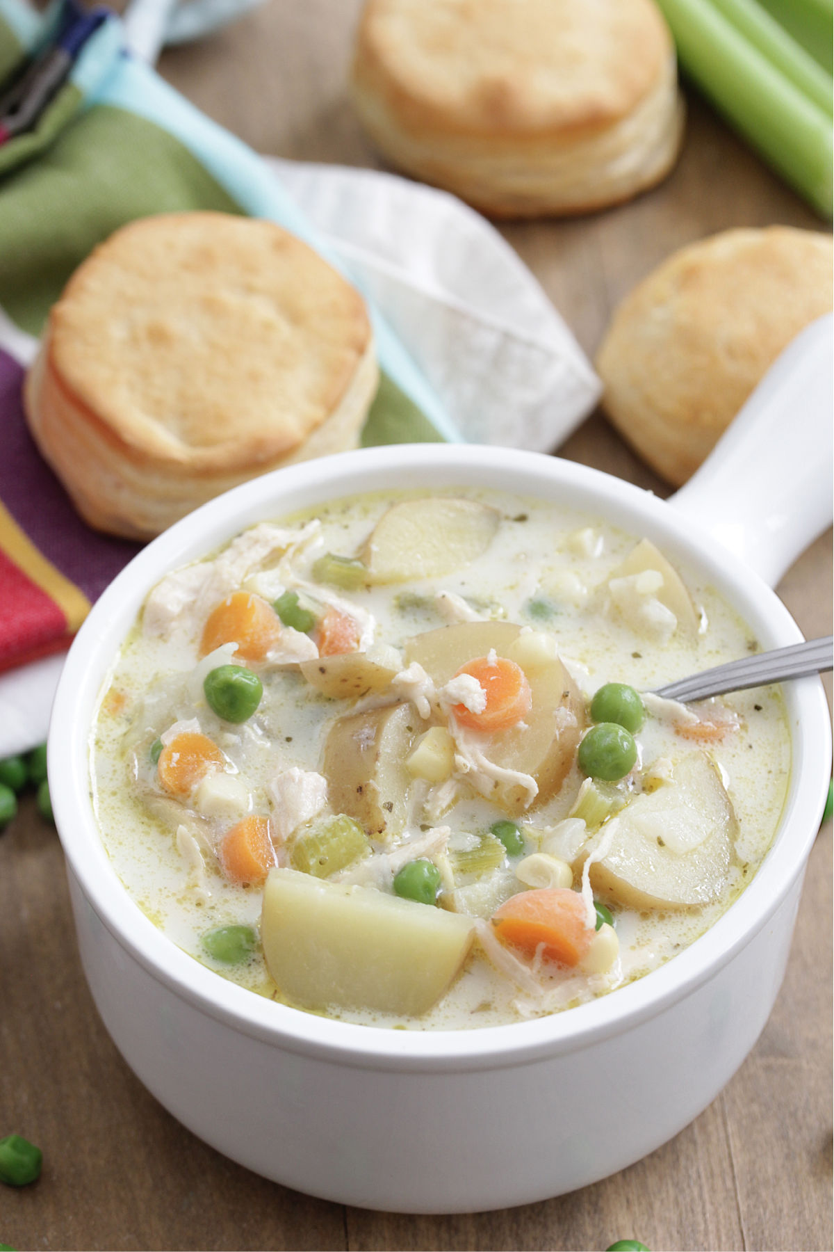 Chicken Pot Pie Soup in a white bowl with biscuits