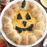 Halloween Buffalo Chicken Dip in a pie dish with jack-o-lantern face