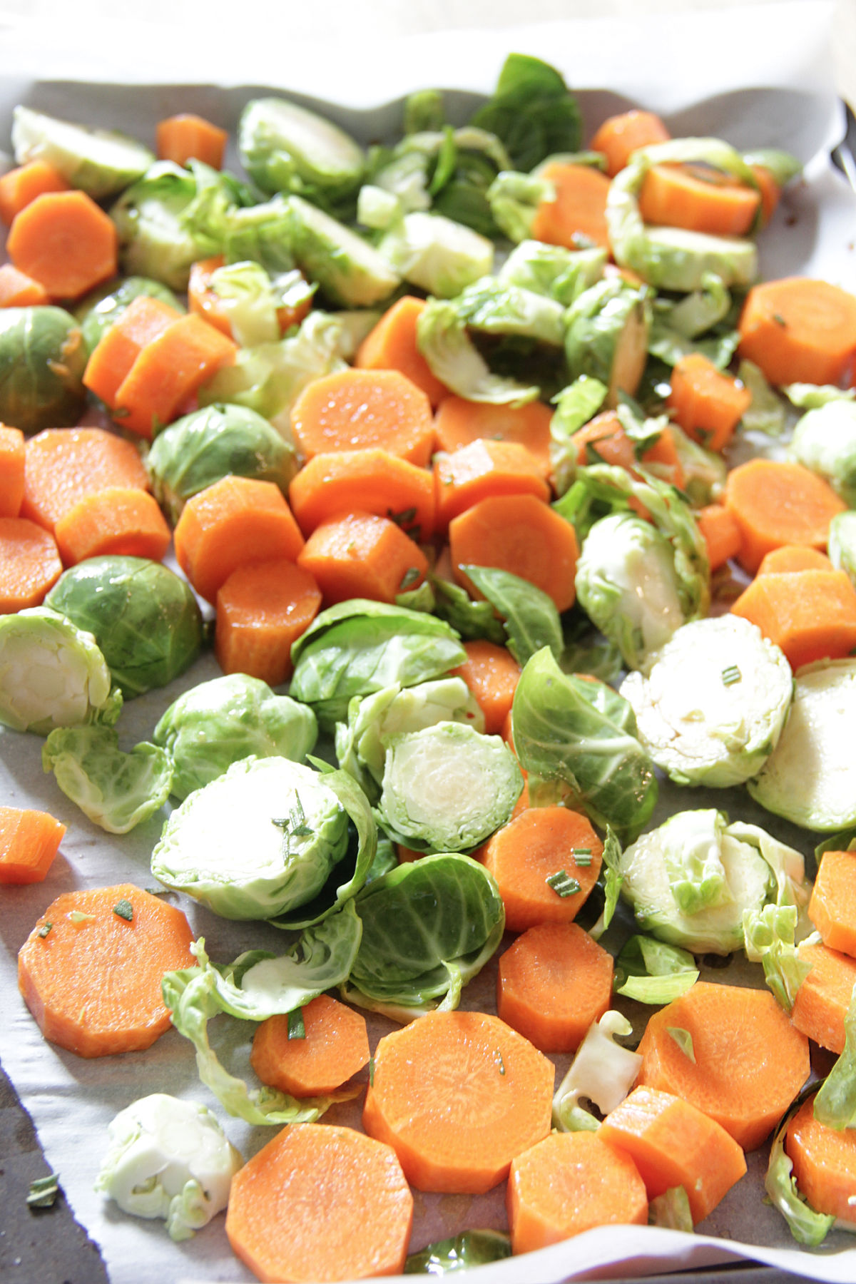 Chopped Brussels Sprouts and Carrots on a sheet pan