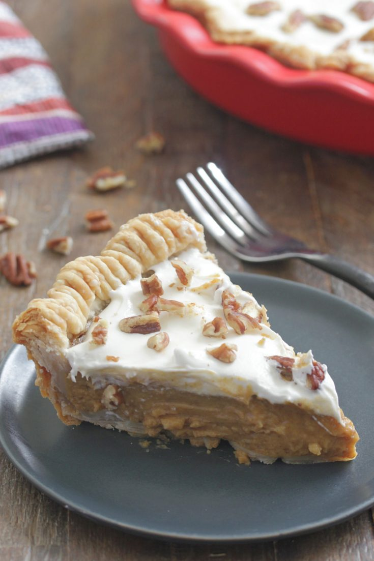 Sweet Potato Pie slice on a blue plate with marshmallow frosting and pecans