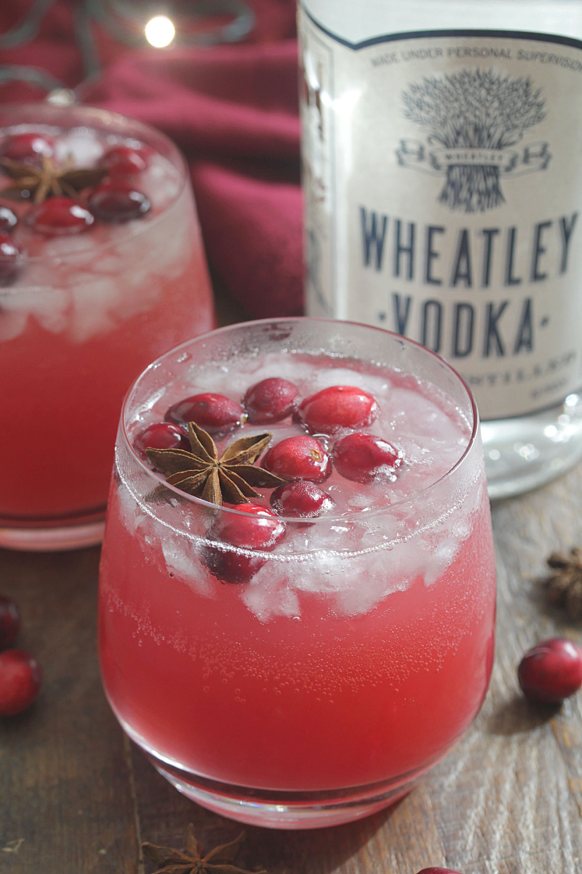 Bottle of Wheatley Vodka next to red holiday drink with cranberries