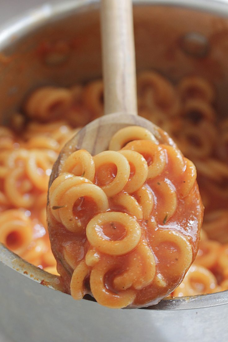 Homemade Spaghettios in a pot with wooden spoon