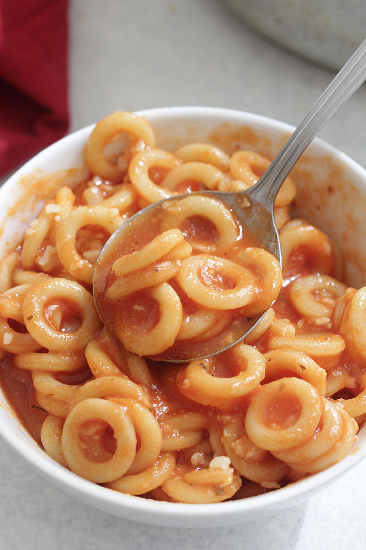 Homemade Spaghettios in a bowl with spoon