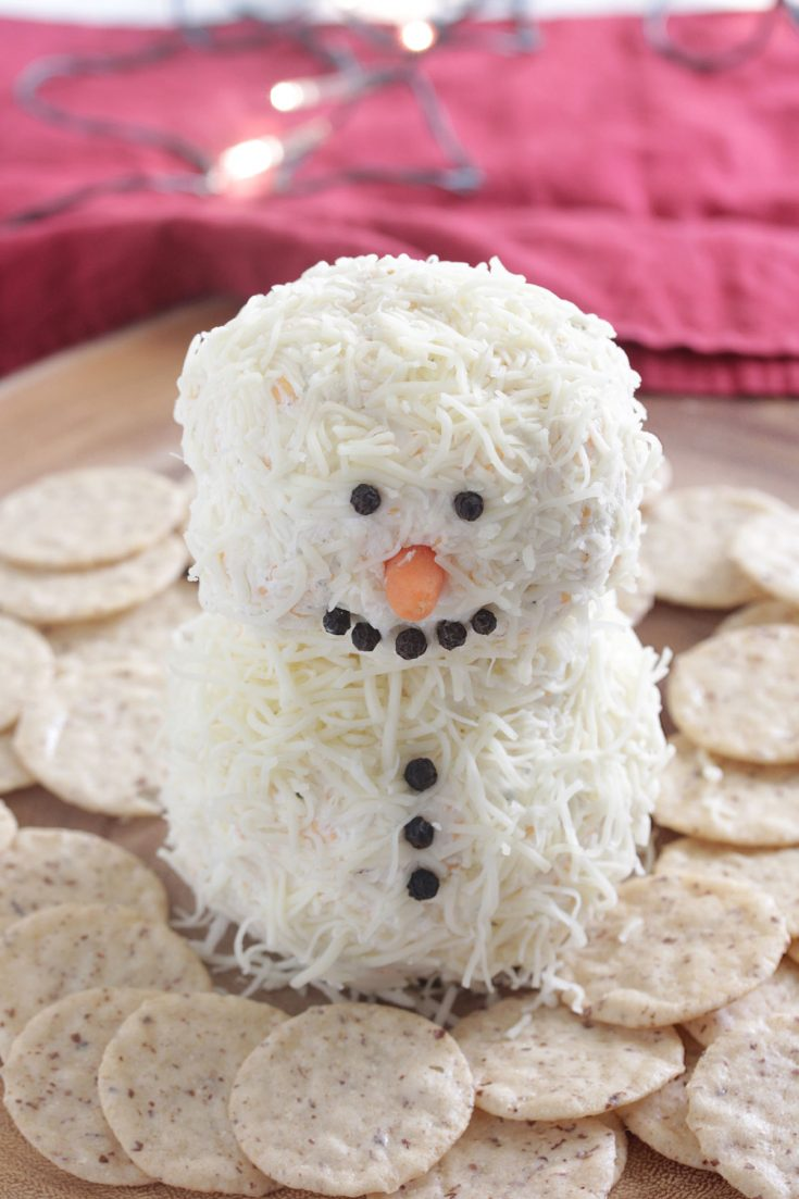 Snowman Cheese Ball on a wooden board with crackers