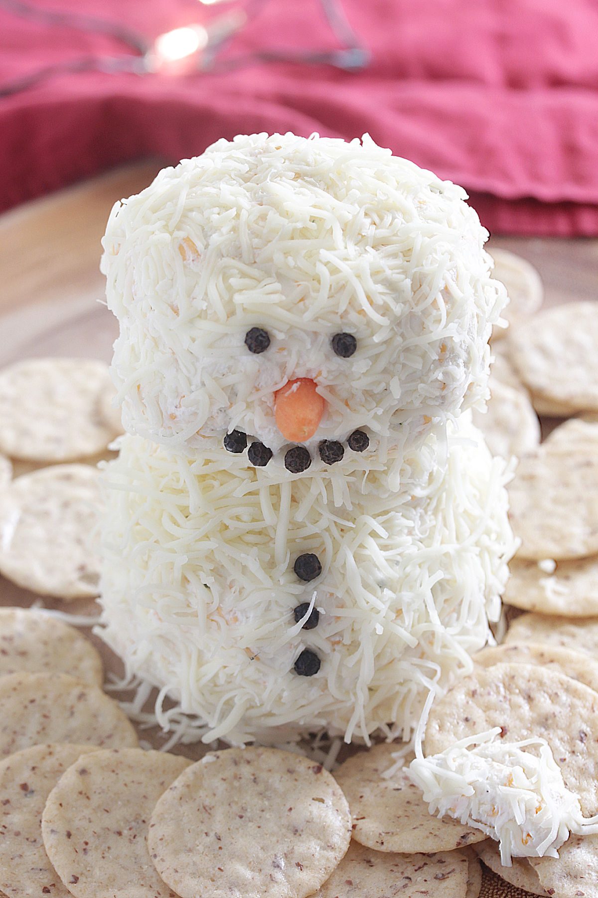 Close up shot of Snowman Cheese Ball on a wooden board with crackers