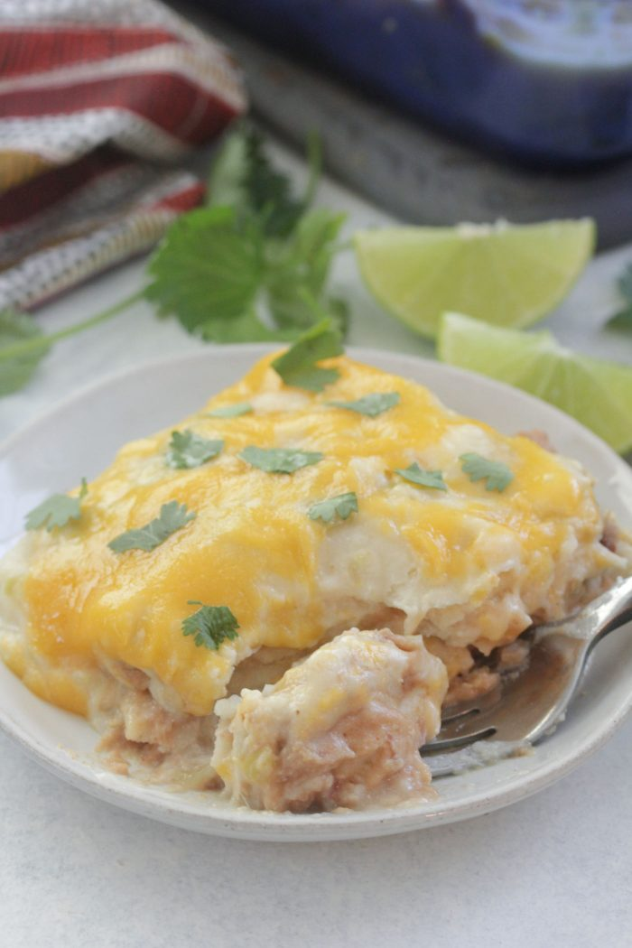White Chicken Enchilada Casserole on a white plate with a fork
